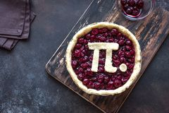 Pi Day Cherry Pie. Making homemade traditional Cherry Pie with Pi sign for March 14th holiday, on wooden background, top view royalty free stock image