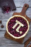 Pi Day Cherry Pie. Making homemade traditional Cherry Pie with Pi sign for March 14th holiday, on wooden background, top view royalty free stock photos