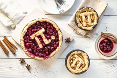 Pi Day Pies. Pi Day Cherry and Apple Pies - homemade traditional various Pies with Pi sign for March 14th holiday, on white wooden background, top view stock photo
