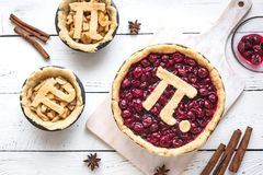 Pi Day Pies. Pi Day Cherry and Apple Pies - making homemade traditional various Pies with Pi sign for March 14th holiday, on white wooden background, top view stock photo