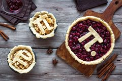 Pi Day Pies. Pi Day Cherry and Apple Pies - making homemade traditional various Pies with Pi sign for March 14th holiday, on wooden background, top view stock photos
