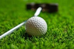 Pi?ka golfowa i putter na trawie fotografia royalty free