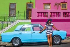 Pi?kna Afryka?ska kobieta w bielu i b??kitnym paskowa? sukni? przed rocznika Ford Cortina tradycyjnymi domami bo i, C fotografia stock
