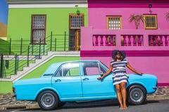 Pi?kna Afryka?ska kobieta w bielu i b??kitnym paskowa? sukni? przed rocznika Ford Cortina tradycyjnymi domami bo i, C zdjęcie royalty free