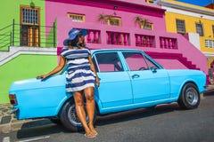 Pi?kna Afryka?ska kobieta w bielu i b??kitnym paskowa? sukni? przed rocznika Ford Cortina tradycyjnymi domami bo i, C fotografia royalty free
