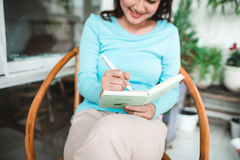Piękna azjatykcia kobieta pisze i pracuje z dzienniczkiem w domu Obrazy Royalty Free
