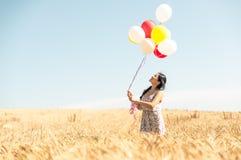 Piękna azjatykcia kobieta w pszenicznym polu z lotniczymi balonami Obrazy Royalty Free
