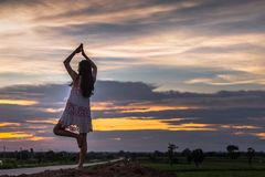 Piękna azjatykcia kobiety pozycja na kopu z zmierzchem Zdjęcia Royalty Free