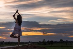 Piękna azjatykcia kobiety pozycja na kopu z zmierzchem Obrazy Stock