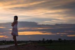 Piękna azjatykcia kobiety pozycja na kopu z zmierzchem Zdjęcie Stock