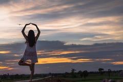 Piękna azjatykcia kobiety pozycja na kopu z zmierzchem Fotografia Stock