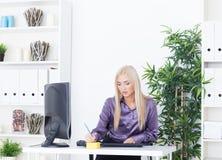 Piękna blondynka przy biurem pisze pióru notatce Zdjęcia Royalty Free