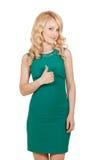 Piękna blondynka w zieleni sukni trzyma kciuk up Zdjęcie Royalty Free