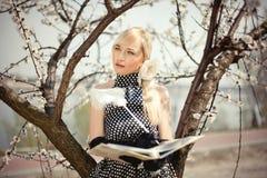 Piękna blondynki dziewczyny pozycja pod drzewem obraz stock
