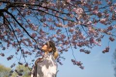 Pi?kna blondynki m?oda kobieta w Sakura Czere?niowego okwitni?cia parku w wio?nie cieszy si? natur? i czas wolnego podczas jej po zdjęcie stock