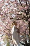 Pi?kna blondynki m?oda kobieta w Sakura Czere?niowego okwitni?cia parku w wio?nie cieszy si? natur? i czas wolnego podczas jej po obrazy royalty free