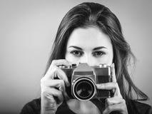 Pi?kna brunetka wskazuje rocznik kamer? zdjęcia royalty free