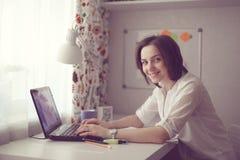 Piękna brunetki kobiety praca przy komputerem w domu Zdjęcia Stock