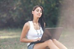 Piękna dziewczyna na internetach przy park2 Zdjęcia Royalty Free