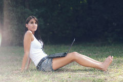 Piękna dziewczyna na internetach przy parkiem Zdjęcia Stock