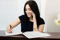 Pi?kna dziewczyna odpowiada wezwanie w stomatologicznym biurze przy recepcyjnym biurkiem fotografia royalty free