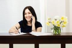 Pi?kna dziewczyna odpowiada wezwanie w stomatologicznym biurze przy recepcyjnym biurkiem zdjęcie stock