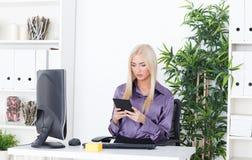 Piękna dziewczyna przy biurem przy komputerem z czytelnikiem Obraz Stock