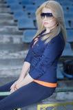 Piękna dziewczyna siedzi na barierze przy stadium Zdjęcia Stock