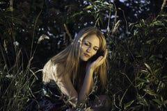 Piękna dziewczyna siedzi w naturze w wieczór Obrazy Stock