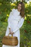 Piękna dziewczyna trzyma kosz w biel sukni Zdjęcia Stock