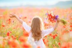 Piękna dziewczyna w makowym polu przy zmierzchem Zdjęcie Stock
