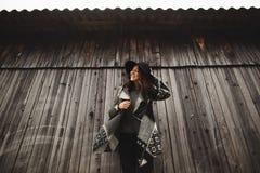Pi?kna dziewczyna z d?ugie w?osy i czarny kapelusz, stojaki na tle rocznika stary drewniany dom zdjęcie stock
