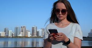 Pi?kna dziewczyna z d?ugie w?osy w okularach przeciws?onecznych u?ywa? smartphone app przy zmierzchu rzecznym quay blisko 4K zbiory wideo