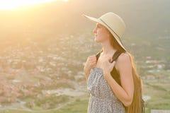 Piękna dziewczyna z plecakiem i kapeluszem stoi z ukosa na tle dolina below i miasto Zdjęcie Royalty Free