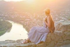 Piękna dziewczyna z plecakiem, kapeluszem i siedzi widok rzeka, góry i miasto below, Fotografia Royalty Free