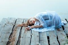 Piękna dziewczyna z smutnym twarzy lying on the beach na drewnianym molu Obraz Stock