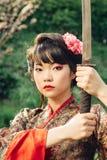 Piękna gejsza w kimonie z samuraja kordzikiem Obrazy Stock