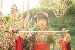 Piękna gejsza w kimonie z samuraja kordzikiem Zdjęcia Royalty Free