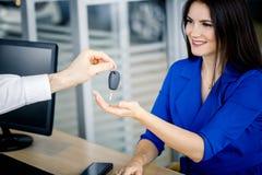 Piękna kobieta bierze samochodu klucz od handlowa Fotografia Stock