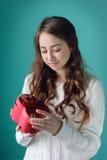 Piękna kobieta considering prezent w postaci serca na walentynka dniu Obraz Stock