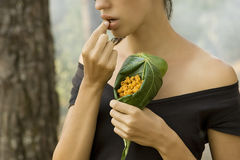 Piękna kobieta je dzikiej malinki w lesie Zdjęcia Stock