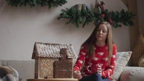 Piękna kobieta jest ubranym zima strój pije herbaty z miodownikiem w domu blisko choinki zbiory wideo