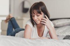 Piękna kobieta opowiada na smartphone w jej sypialni Zdjęcie Royalty Free