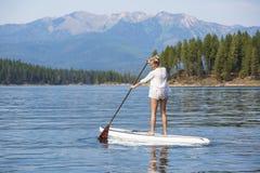 Piękna kobieta paddleboarding na scenicznym halnym jeziorze Zdjęcia Stock