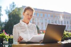 Piękna kobieta patrzeje przez dokumentów na restauracja tarasie Zdjęcie Royalty Free