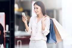 Piękna kobieta patrzeje w telefon komórkowego z torba na zakupy Obrazy Stock