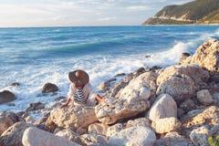 Piękna kobieta relaksuje przy morzem z kapeluszem Zdjęcia Stock