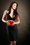 Piękna kobieta trzyma czerwonego serce na czerni Obrazy Royalty Free