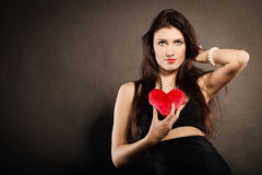 Piękna kobieta trzyma czerwonego serce na czerni Zdjęcia Royalty Free