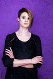 Piękna kobieta w czerni sukni na purpurowym tle zdjęcia stock